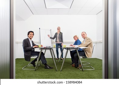 Small business meeting, with four people in a small stylish conference room with grass on the floor, discussing strategy, growth, sustainability and environmental inpact of business,