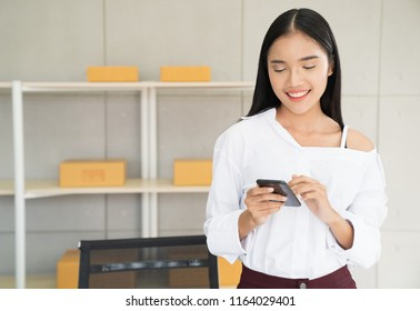 Small business owner, Asian woman hold smartphone check online order, online marketing packaging boxes and delivery, SME concept. Young Owner People Start up for Business Online