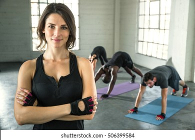 Small business owner of athletic gym smiling trainer instructor posing for a portrait with students