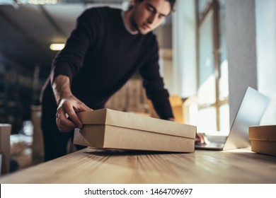Small business owner with the box for shipping working on laptop. Male entrepreneur working on online orders.