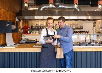 Small business owner couple in little family restaurant looking at tablet for online orders – concept of family business with young entrepreneurs running restaurant with online food delivery