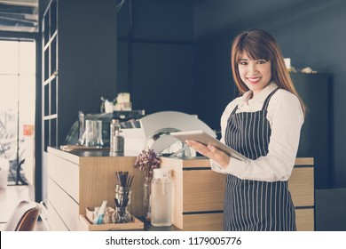 small business owner holding tablet at counter in coffee shop. asian female barista wearing apron using touchpad at bar in cafe. food service, restaurant concept.