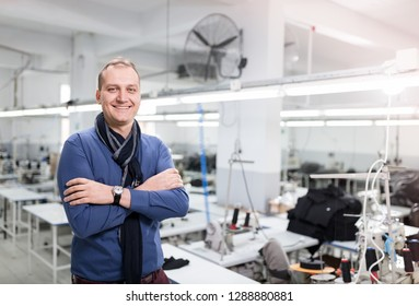 Small business owner posing in factory.