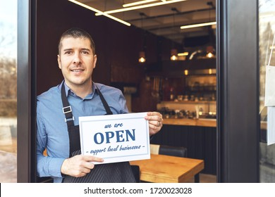 Small business owner smiling while holding open sign of restaurant reopening after lockdown quarantine due to coronavirus pandemic - Entrepeneur opening cafeteria activity to support local businesses.