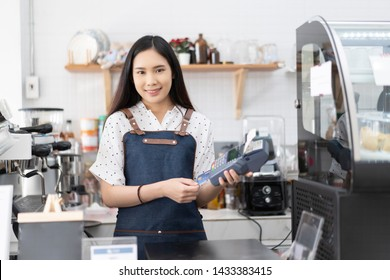 Small business owner startup woman receives credit card from customer paying contactless NFC. Asian barista girl slip on credit card reader machine at bar counter cafe restaurant,cashless technology