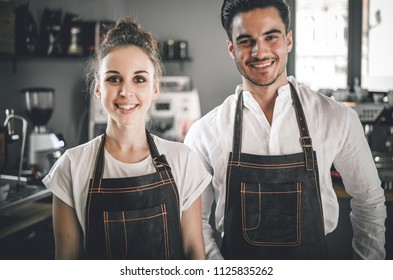 Small business owner, successful young baristas standing in front of their cafe