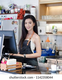 Small business owner using digital device for payment small business owner in front of storeIn Coffee Shop