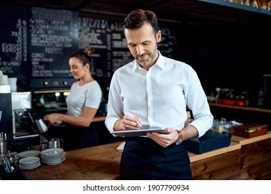 Small business owner using digital tablet standing in cafe