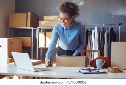 Small business owner. Women, owner of small business packing product in boxes preparing it for delivery.