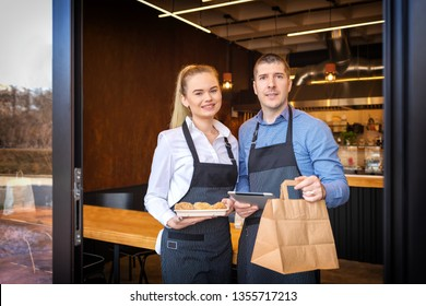 Small business owners couple standing in doorway of trendy restaurant delivering to go orders and attending new customers – Man and woman keeping bistro on top with digital technologies