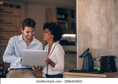 Small business owners using laptop in their restaurant. Smiling man and woman working in their restaurant.