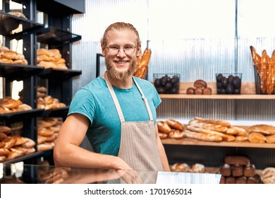 Small business and ownership concept. Happy young adult male working in family bakery, standing near fresh wholegrain bread and smiling wide