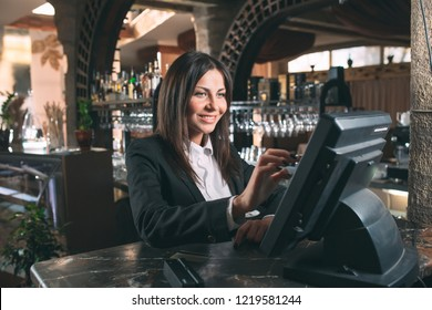 small business, people and service concept - happy woman or waiter or manager in apron at counter with cashbox working at bar or coffee shop