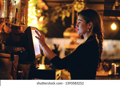 small business, people and service concept - A young waitress at counter in a small bar or restaurant
