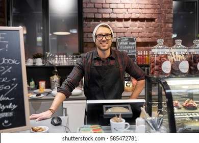 small business, people and service concept - happy seller man or barman at counter with cashbox in vegan cafe or coffee shop