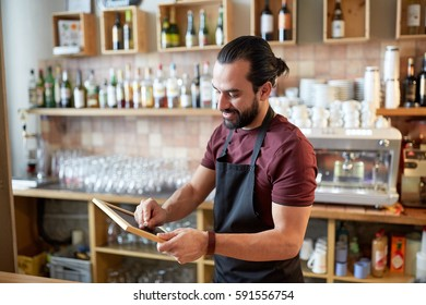 small business, people and service concept - happy man or waiter in apron with black chalkboard banner at bar or coffee shop