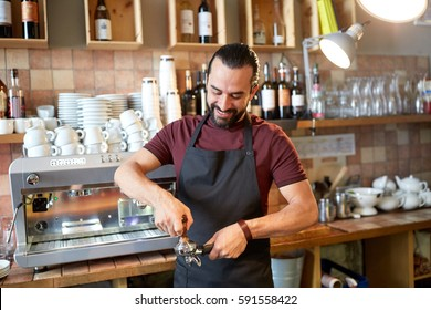 small business, people and service concept - happy man or waiter in apron with holder and tamper preparing espresso at coffee shop