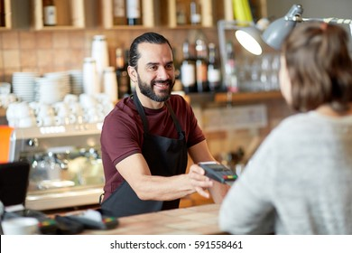 small business, people and service concept - happy man or waiter in apron with card reader and customer paying at bar of coffee shop