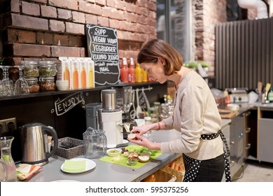 small business, people and service concept - happy woman or barmaid cooking at vegan cafe