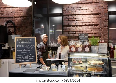 small business, people and service concept - happy bartenders at cafe or coffee shop counter