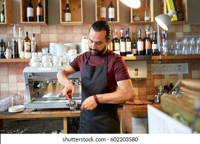 small business, people and service concept - man or waiter in apron with holder and tamper preparing espresso at coffee shop