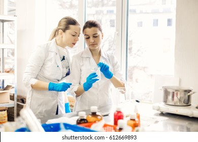 Small business people at work. Two young womens are working at their laboratory of cosmetic production.