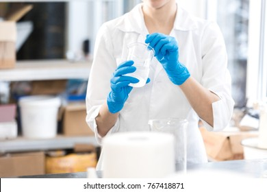 Small business people at work. Young woman working at the laboratory of cosmetic production. Mixing ingredients. Young technologist making face care creams. Private small cosmetic products factory.