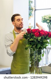 small business, sale and floristry concept - florist or seller setting red roses at flower shop