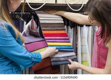 Small business, shop, show room of fabrics and accessories for the interior. Women are watching patterns