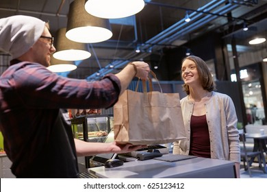 small business, takeaway food, people and service concept - man or seller giving paper bag to happy female customer at vegan cafe