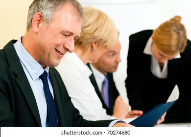 Small business team in the office in front of a whiteboard discussing a project and some documents