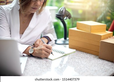 Small business woman Worker delivery service and working packing box, business owner working checking order to confirm before sending customer in post , Shipment Online with barcode scanner clipboard.