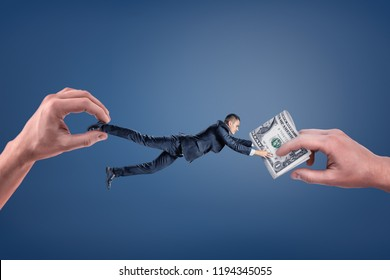 A small businessman caught between two giant hands, one giving him money and another tugging away from them. Carrot and stick. Money as incentive. Caught red-handed.