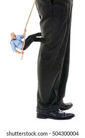 Small businessman climbing big business player's leg