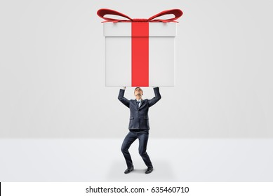 A small businessman holding a giant gift box with both hands above his head. Presents for customers. Promotions and sales. Business marketing.