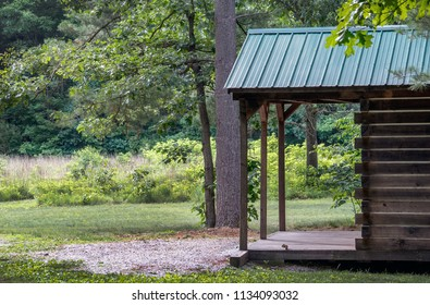 A small cabin is nestled in the woods waiting for campers, and a tiny chipmunk sits on the porch as a welcoming committee of one