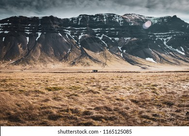 Small cabin under a massive rock formation in a valley on Iceland, showing the scale of icelandic countryside