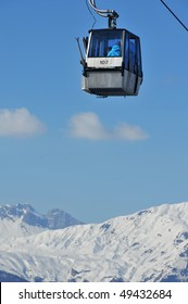 a small cable car for skiers with snow covered mountains in the background