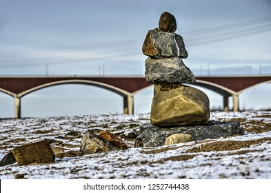 Small cairn on the snow-covered floodplain of the river Waal near Nijmegen, The Netherlands, with city bridge De Oversteen (The Crossing) blurred  in the background