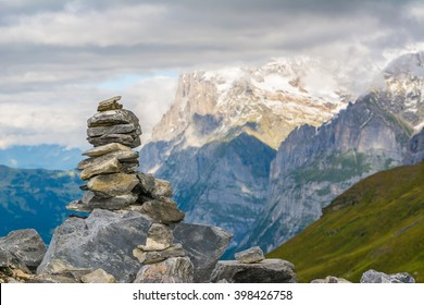 Small cairn with snowy alpine mountains at background