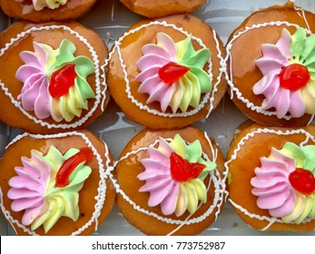 Small cake decorated with colorful butter cream and fruit jam