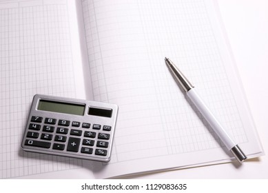 Small calculator and ballpoint pen on a account book