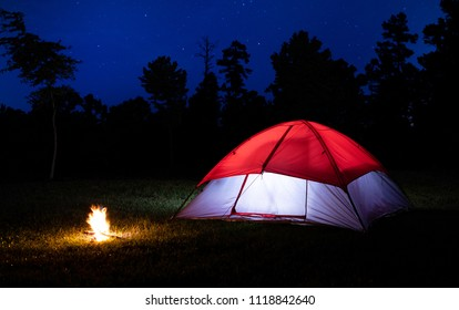Small campfire next to lit tent with stars in the sky above