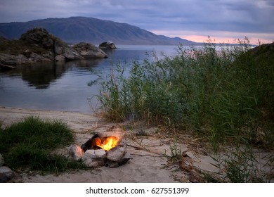 Small campfire on the shore of Lake Bukhtarma in Eastern Kazakhstan