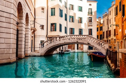 Small canals for boats, old brick houses Venetian style in Venice, Italy.