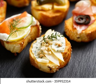 Small canape, crostini  with grilled baguette with the addition of blue cheese,apple slices, cashew nuts and fresh thyme on black background. Delicious appetizer