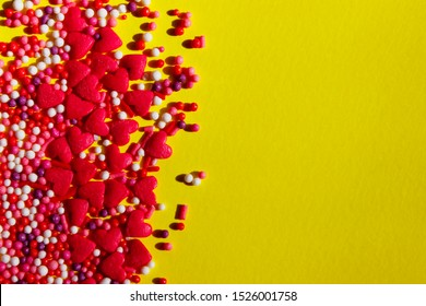 Small candies in the shape of hearts and balls are on a yellow background. Colorful candies over yellow background with a lot of space for text. Food, holidays concept.
