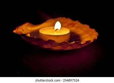 A small candle burning in a scallop shell, a table decoration, on black background