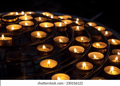 Small candles burn in dark interior of Catholic cathedral
