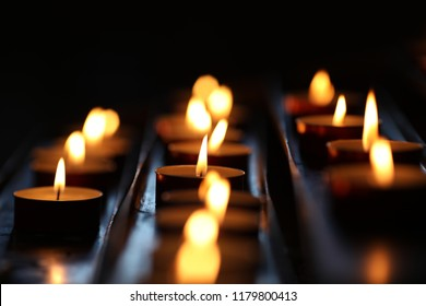 small candles, in a church. votive candles and thanksgiving. votive candle is a small candle intended to be burst as a votive offering in a act of Christian prayer